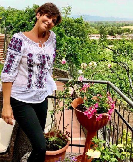 Giornalista Sky TG24 Valentina Bendicenti mentre sorride guardando i fiori